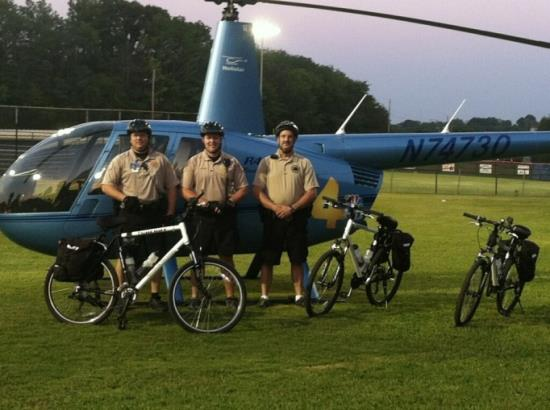 Bicycle Team Group Photo, Standing in Front of a Helicopter with their Bicycles